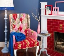 Choosing only a select few colours is key to a cohesive colour scheme. Here Resene True Blue contrasts perfectly with the pinks and reds of the chair, photo frames, and fireplace.