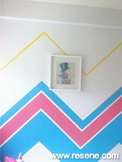 Feature wall in the bedroom - a chevron pattern using Resene Claret Resene Hullabaloo and Resene