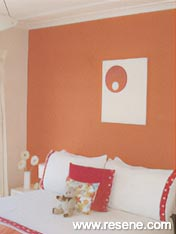 Resene Wan White with a feature wall of Resene Fireball bedroom