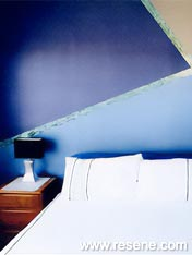 Bedroom with a feature wall painted in abstract shapes